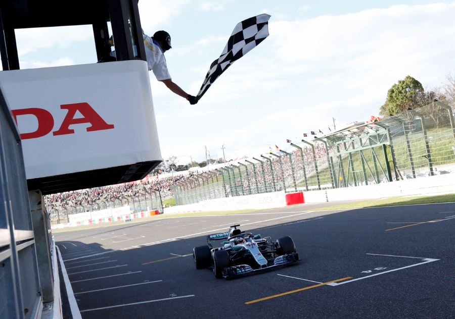(FILES) This file photo taken on October 7, 2018 shows Mercedes' British driver Lewis Hamilton crossing the finish line during the Formula One Japanese Grand Prix in Suzuka. - Lewis Hamilton may not be able to clinch a sixth world championship at the typhoon-threatened Japanese Grand Prix on October 13, 2019, but knows he can knock all but teammate Valtteri Bottas out of the title race. (Photo by ISSEI KATO / POOL / AFP)