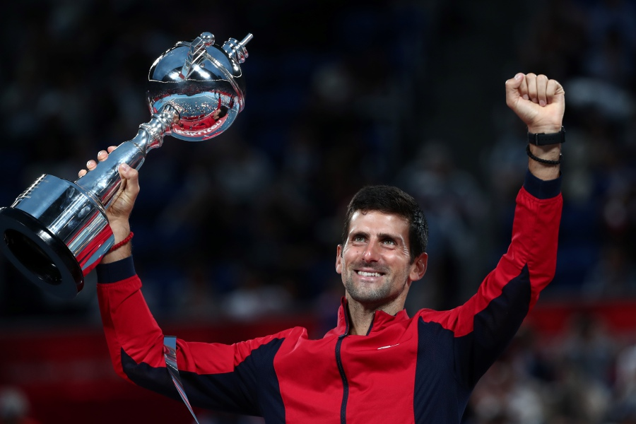 Serbia's Novak Djokovic celebrates with the trophy after winning the men's singles final against John Millman of Australia at the Japan Open tennis tournament in Tokyo on October 6, 2019. (Photo by Behrouz MEHRI / AFP)