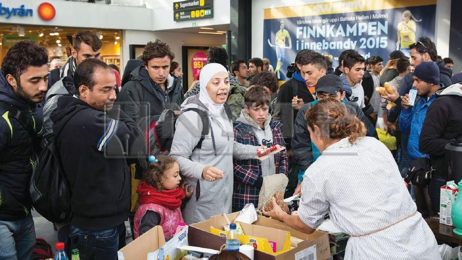 Volunteers distributing food and drinks to migrants in conjunction with Giving Tuesday celebration at Malmo train station in Sweden in 2016. REUTERS PIC