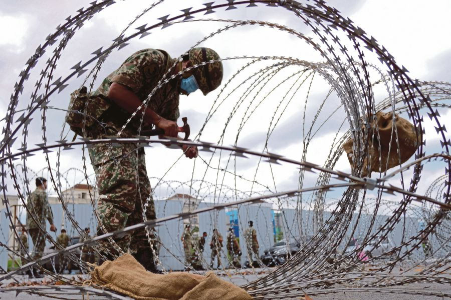 An armed forces personnel dismantling the concertina wires following the government's decision to  end the Enhanced  Movement Control Order at Putra Point in  Nilai yesterday.  --BERNAMA pic