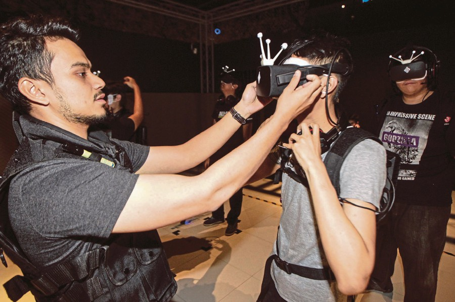 Suit up: An EXA Global staff helping a player with the VR gear. Pix by Osman Adnan