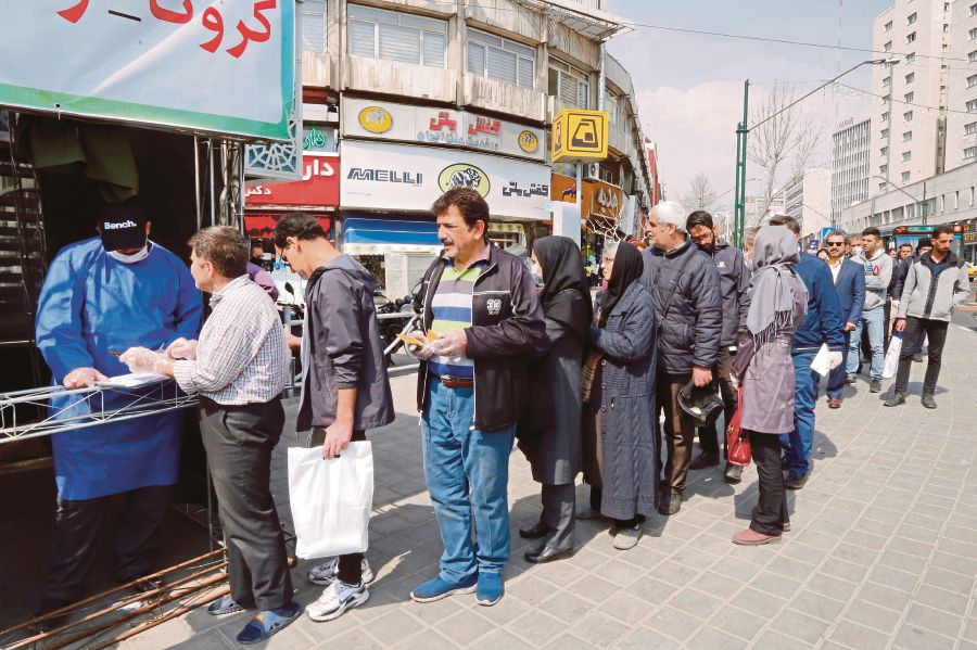People queuing to receive packages for precautions against Covid-19  in Teheran in March. Iran's desperate need for  medical equipment and medication by relaxing sanctions has  been rejected by the US. -AFP pic