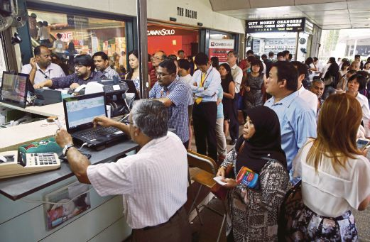 People queuing up outside moneychangers at the central business district in Singapore. While Singaporeans are spending more in Malaysia following the depreciation of the ringgit, some remain cautious with money. Reuters pic