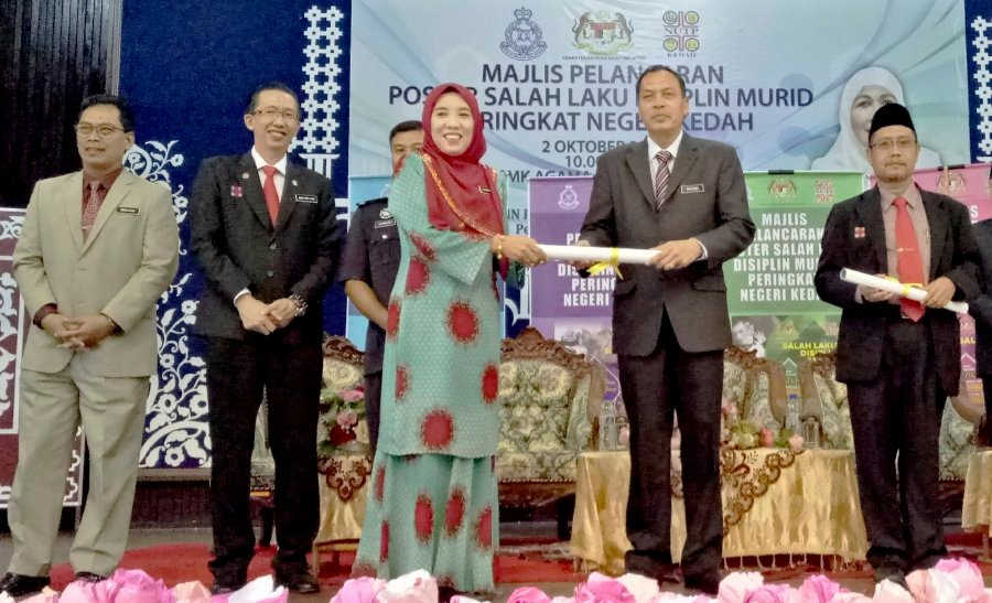 1768b6a3b3b Kedah Education Department s school management sector head Rozaini Ahmad  (second from right) at the presentation ceremony of disciplinary posters to  ...