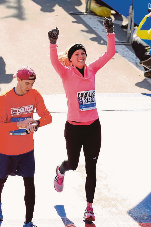 Denmark's Caroline Wozniacki celebrates as she crosses the finish line in the New York City Marathon in Central Park on Sunday. AFP pic