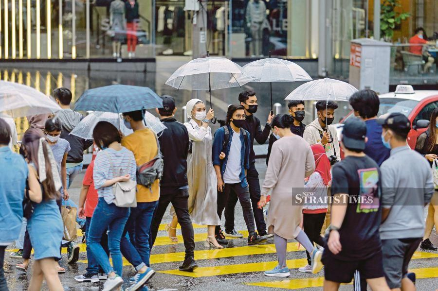 People in face masks walking in the rain in Kuala Lumpur yesterday. PIC BY AIZUDDIN SAAD