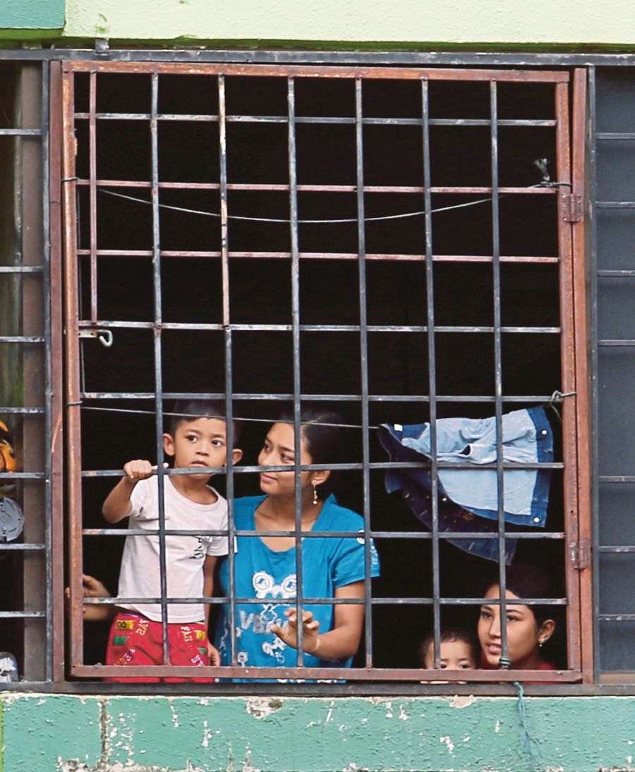 Residents of a flat near the Kuala Lumpur Wholesale Market looking out their window during the Movement Control Order. -NSTP/EZAIRI SHAMSUDIN/NSTP