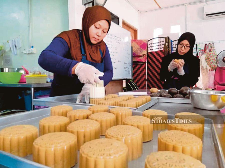 Noor Asmah Mohamed Moktar (left) baking halal mooncakes in a variety of flavours. - NSTP/Goh Pei Pei