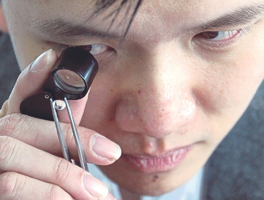 Ziyin inspecting a loose diamond closely to determine its quality.