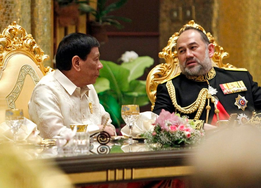 Yang di-Pertuan Agong Sultan Muhammad V speaks to Philippines President Rodrigo Duterte (left) during the royal banquet as part of the Golden Jubilee celebrations at Nurul Iman Palace. EPA-EFF