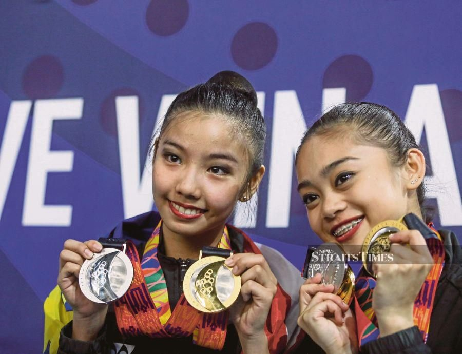 Izzah Amzan (right) and Koi Sie Yen with their medals in Manila yesterday. NSTP/OSMAN ADNAN