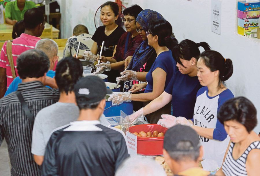 (File pix) Pit Stop Community Cafe volunteers at the serving station. Pix by Khairull Azry Bidin