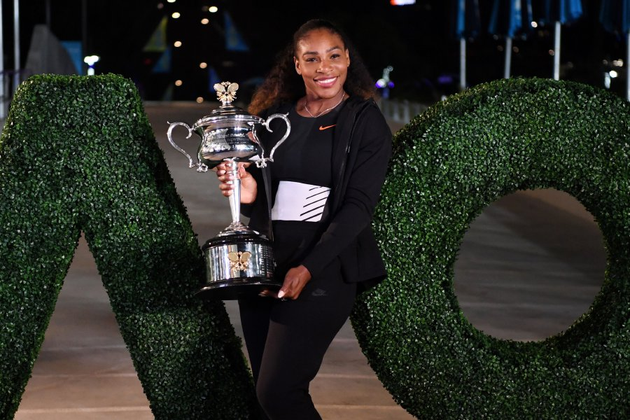 """(File pix) This photo taken on Jan 29, 2017 shows Serena Williams of the US posing with the championship trophy after her victory against Venus Williams of the US in the women's singles final at the Australian Open tennis tournament in Melbourne. Williams will be ready for the Australian Open with her return to Melbourne for the season's opening Grand Slam """"very likely"""", organisers said on December 6, 2017. AFP Photo"""