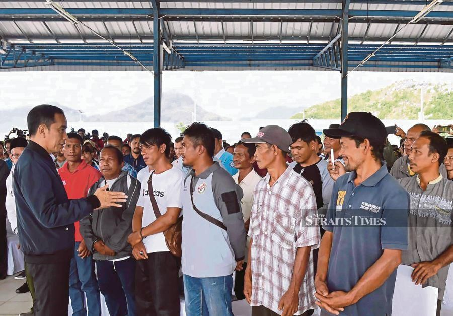"This handout picture taken and released on January 8, 2020 by the Presidential Palace shows Indonesia's President Joko Widodo (L) speaking to fishermen during his visit to the Natuna islands, which border the South China Sea. - Indonesia has deployed fighter jets and warships to patrol islands near the disputed South China Sea, the military said on January 8, escalating tensions with Beijing after a diplomatic spat over ""trespassing"" Chinese vessels. AFP"