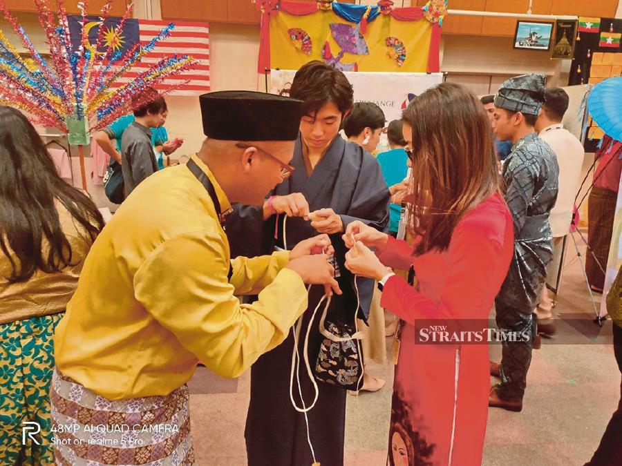 A Malaysian Participating Youth teaching the PYs from other countries how to play the gasing at the National Youth Centre in Tokyo, Japan.