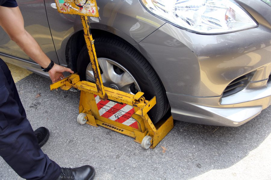 (File Pix) An MPSJ officer clamping the tyre of a car during a recent operation.
