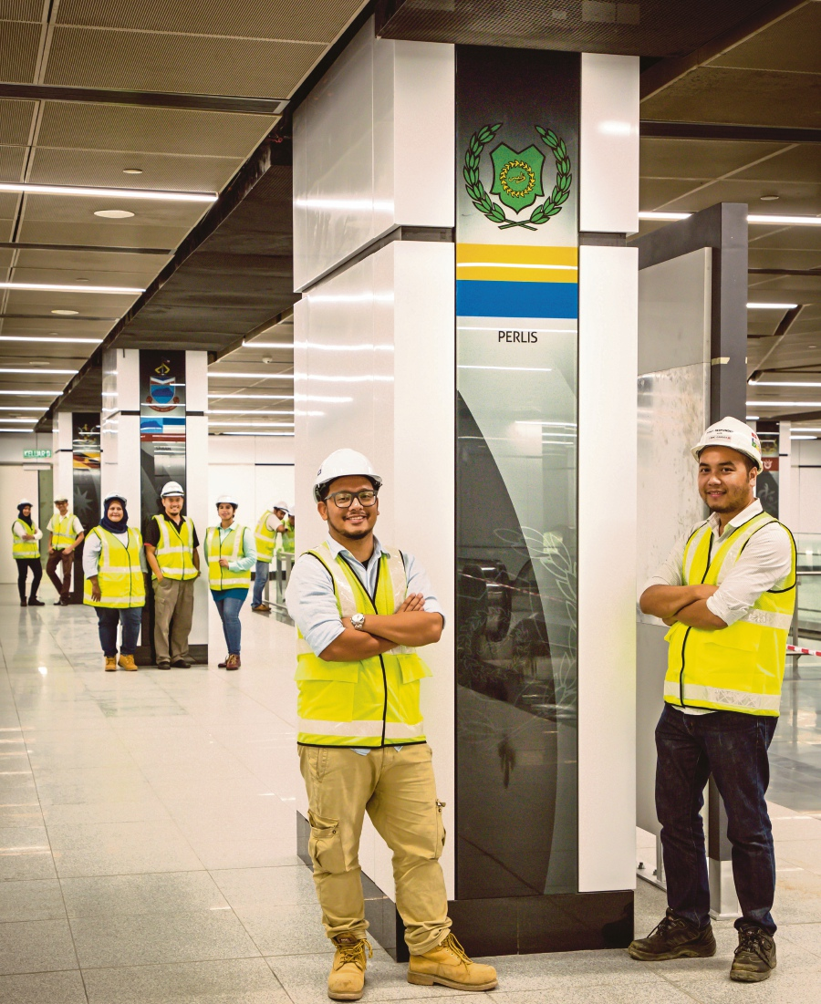 The beaming and proud engineers in the MRT Merdeka underground station where every state flag is featured on each pillar