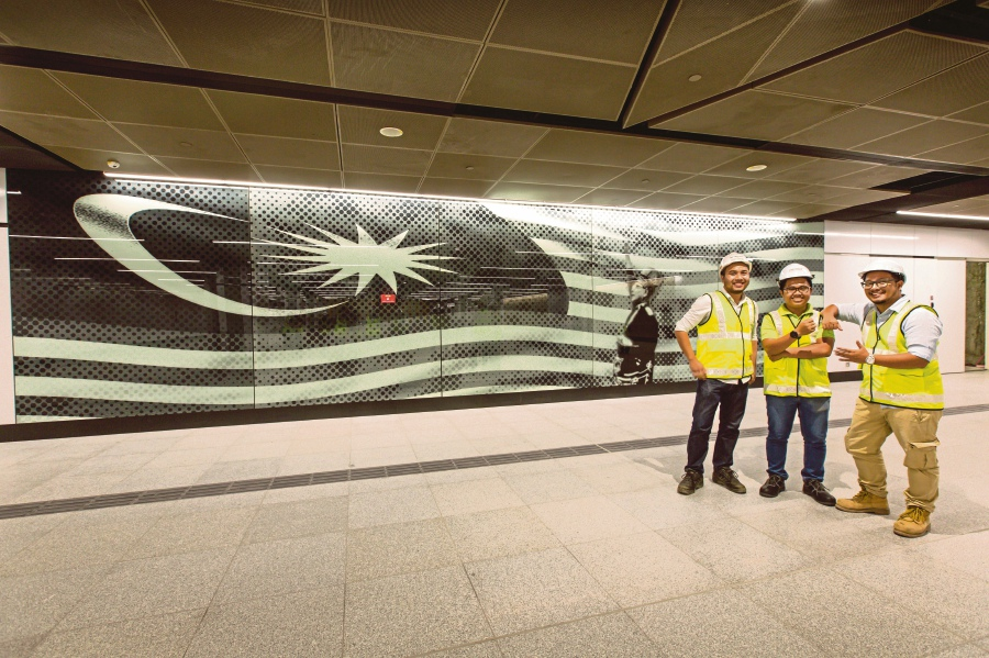 The underground team standing at two feature walls in the MRT Merdeka station which feature detailing of the Rukun Negara and Jalur Gemilang