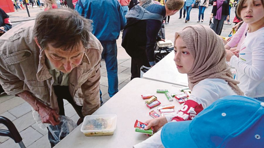 A homeless man taking a closer look at the food package he is getting from a volunteer.