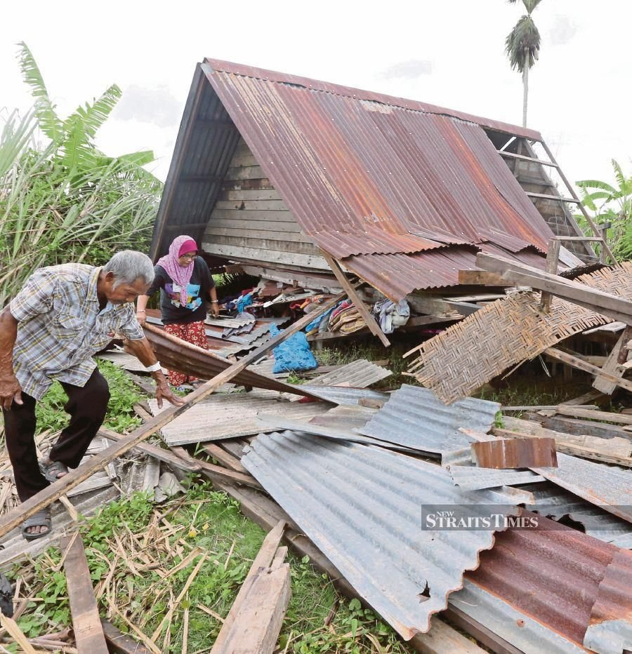 Ahmad Kancil and his wife, Rohani Saad, searching for their belongings after their house was damaged in the storm in Kampung Sempering, Perlis, on Friday night. PIC BY SHAHRIZAL MD NOOR