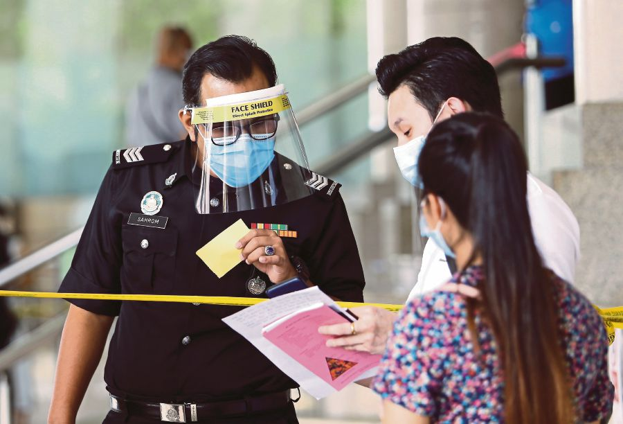 An Immigration officer helping a man with his passport-renewal application in Putrajaya on May 6.  Digitalisation of government delivery services will     reduce the need for people to visit counters at government agencies.