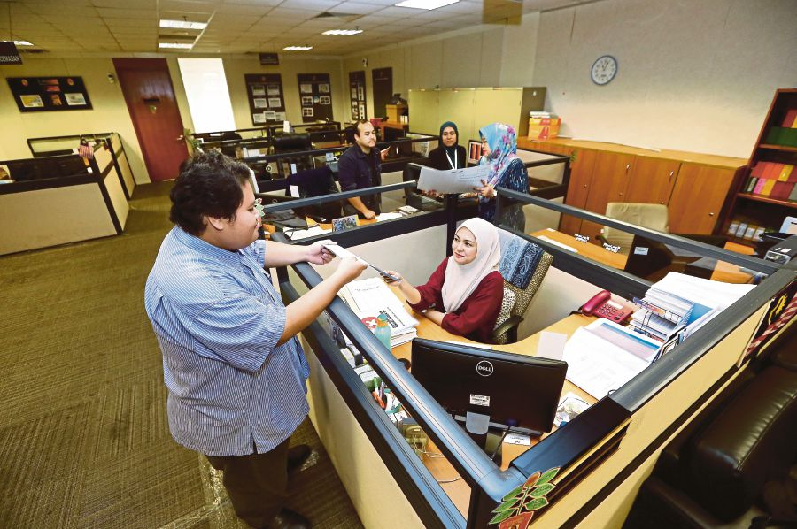 Civil servants working at the Home Ministry in Putrajaya on May 4.  Government workers who  are affected by the reduction or closure of   counters at public agencies can embark on reskilling. FILE PIX