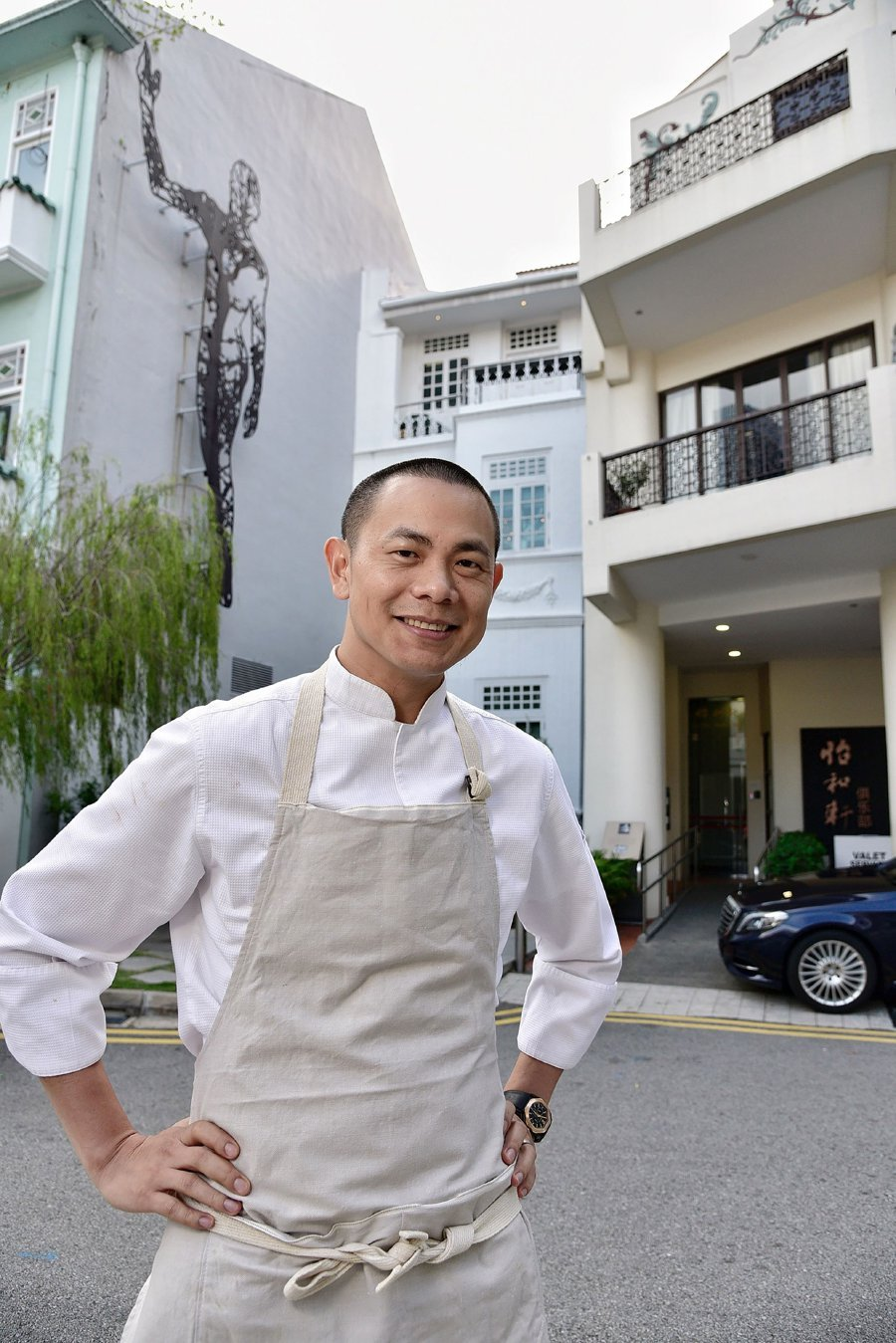 """This photograph taken on Oct 11, 2017 and made available by The Straits Times shows chef-owner Andre Chiangposing outside his two-Michelin-starred restaurant """"Andre"""" in Singapore. A Singapore chef with two Michelin stars has announced he wants to be stripped of the honour and will close his popular eatery, the latest restaurateur to walk away from the culinary distinction. (AFP PHOTO)"""
