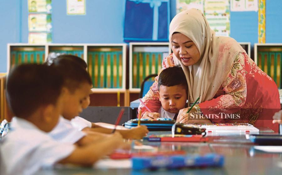 A teacher helping a pupil on the first day of school at SK Setiawangsa, Kuala Lumpur. The higher purpose of education is to become a better human being. PIC BY MOHAMAD SHAHRIL BADRI SAALI