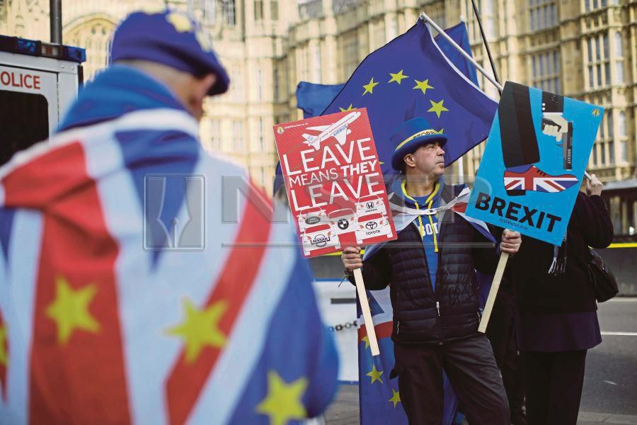 Anti-Brexit protesters holding EU flags and placards outside Parliament in London on Tuesday. AFP PIC