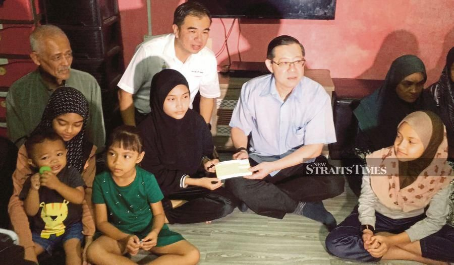 Finance Minister Lim Guan Eng handing a cheque for RM5,000 to Nur Afni Nirwana, the eldest of Khairizul Mohamad Noor's five children, at Kampung Bagan Jermal in Butterworth yesterday. PIC BY DANIAL SAAD