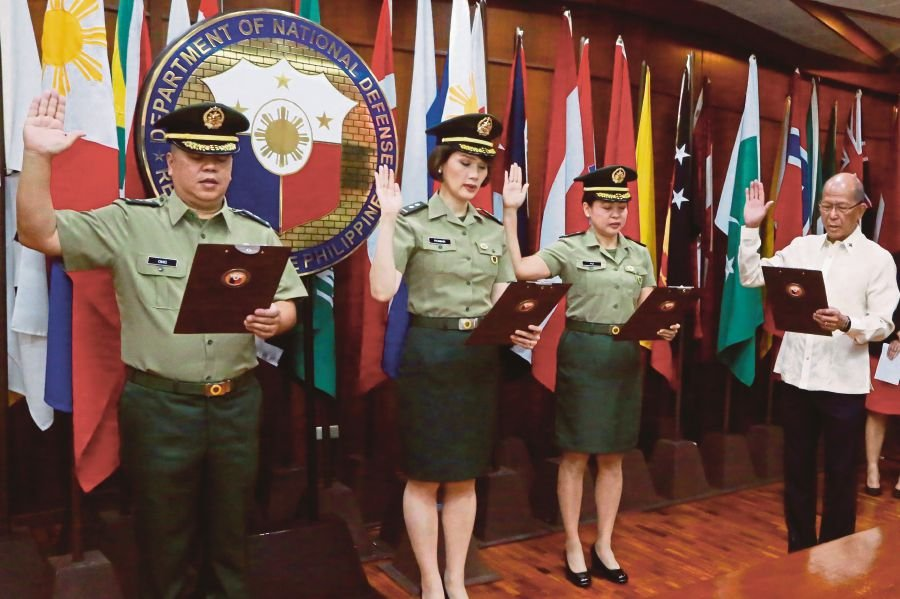 This handout photo taken on February 14, 2018 and released by the Department of National Defense (DND) shows Philippine Defense Secretary Delfin Lorenzana (right) leading the oath-taking for newly-appointed lieutenant colonel and congressman, Edwin Marino Ongchuan of Northern Samar (left), Congresswoman Divina Grace Yu of Zamboanga Del Sur's First District (2nd right), and Congresswoman Geraldine Roman (centre) as reservist officers in the Philippine Army during a ceremony at the defense office in Camp Aguinaldo in Quezon City, suburban Manila. In May 2016 Geraldine Roman became the first transgender politician to win a congressional seat in the predominantly Catholic Philippines. AFP
