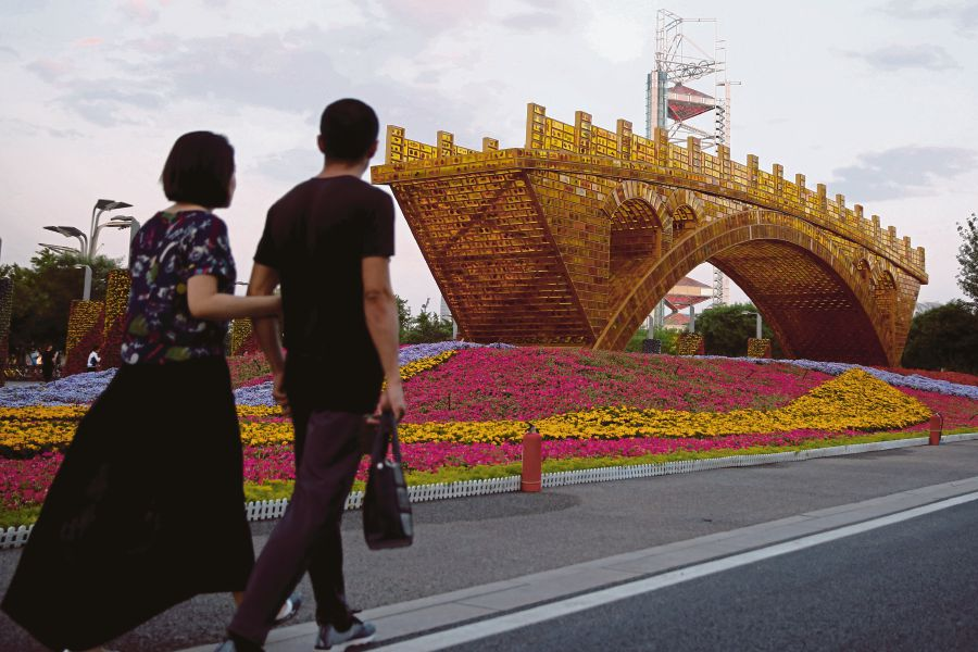 People walking past the installation 'Golden Bridge on Silk Road' by artist Shu Yong in conjunction with the Belt and Road Forum for International Cooperation in Beijing. China is charting a 'win-win' partnership through this forum. REUTERS PIC