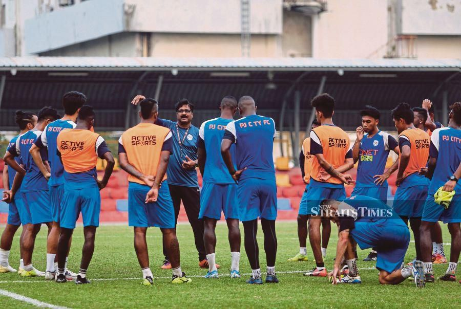 PJ City coach K. Devan (second from left) has a pep talk with his players during training.