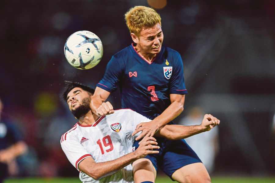 Thailand's Theerathon Bunmathan (back) fights for the ball with United Arab Emirates' Jassim Yaqoob Albalooshi in a World Cup qualifier in Bangkok on Tuesday. Thailand won 2-1. -AFP