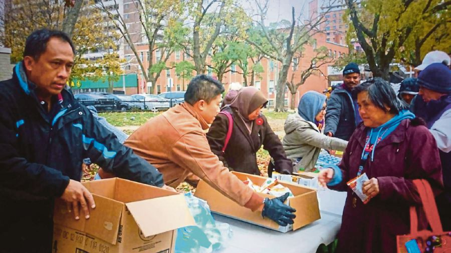The Muslim community from Malaysia and Singapore handing out food to the homeless at Moss Park in Toronto.