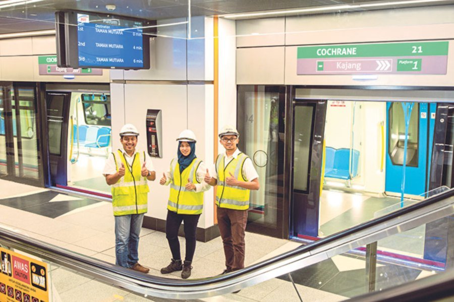 Ruslan, Arziah and Ahmad standing proud in the Cochrane MRT station as SBK Line 1 Phase 2 opens for operation in July 2017.