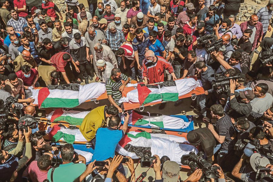 Palestinians attending the funeral of 10 members of the Abu Hatab family in Gaza City on  May 15. They were killed in  an Israeli airstrike on the Al-Shati refugee camp in the Gaza Strip. - EPA PIC