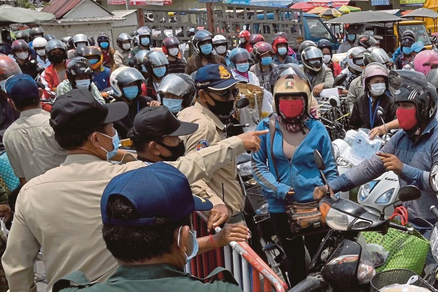 Police block motorists from passing a checkpoint due to lockdown restrictions introduced to try to halt a surge in cases of the Covid-19 coronavirus in Phnom Penh on April 17. - AFP pic