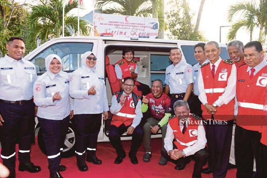 Malaysian Red Crescent Society chairman Tan Sri Tunku Puteri Intan Safinaz Almarhum Sultan Abdul Halim seated inside the ambulance, which was handed over to the agency by Deputy Finance Minister Datuk Amiruddin Hamzah (seated, wearing round neck T-shirt) recently.