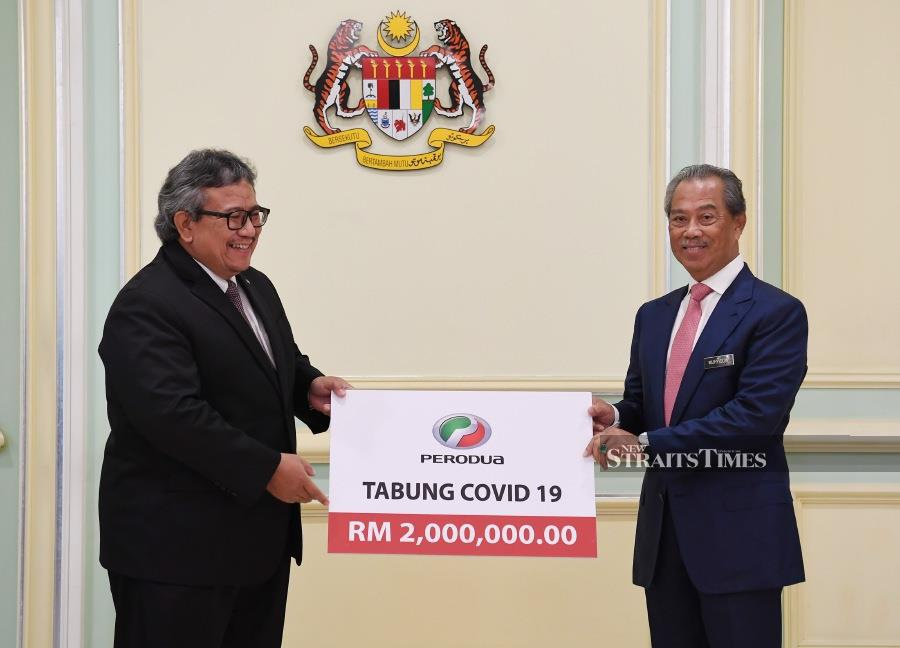 Perodua president and chief executive officer Datuk Zainal Abidin Ahmad presents the contribution to Prime Minister Tan Sri Muhyiddin Yassin at his office earlier today. NST pix by Ghazali Kori