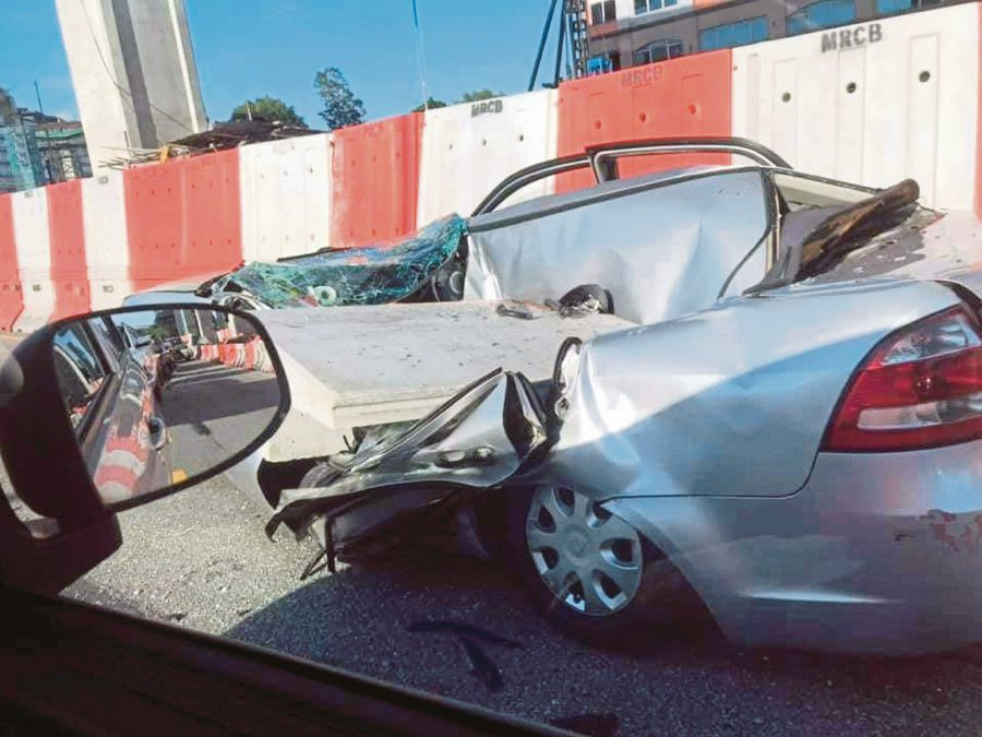 This Sept 19 picture shows a concrete slab crashing on a car near the construction of the Sungai Besi-Ulu Klang Elevated Expressway (SUKE) in Kuala Lumpur.  -Pic courtesy of NST reader.