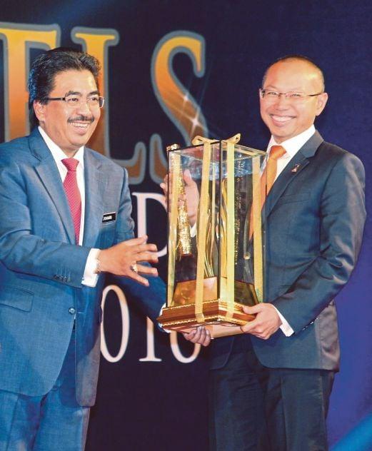 Second Finance Minister Datuk Johari Abdul Ghani presenting the Jewel of Muslim World Award 2016 to Permodalan Nasional Bhd group chairman Tan Sri Abdul Wahid Omar at the 7th Muslim World Biz 2016 in Kuala Lumpur yesterday. Pic by Yazit Razali