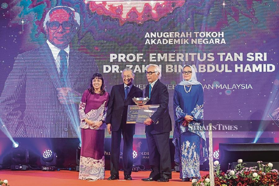 Prime Minister Tun Dr Mahathir Mohamad (second from left) handing over the National Academic Laureate Award prize and trophy to Zakri Abdul Hamid at the Education Ministry's 13th National Academic Awards. Looking on are Deputy Education Minister Teo Nie Ching (left) and Higher Education Minister director-general Datuk Dr Siti Hamisah Tapsir. -NSTP/Aizuddin Saad