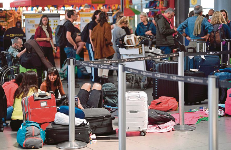 Stranded passengers at the El Dorado International Airport in Bogota, Colombia, on Thursday. The nation will block all international flights from Monday for 30 days to prevent the spread of Covid-19. -AFP pic
