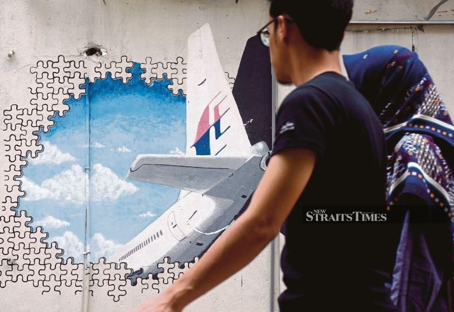 People passing by a mural of Flight MH370. NSTP File pic