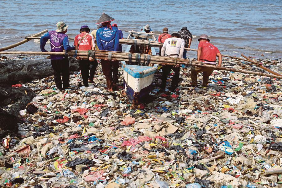 Fishermen struggling to get a boat to sea through a swath of plastic waste choking Sukaraja beach in Bandar Lampung, Sumatra recently. -AFP