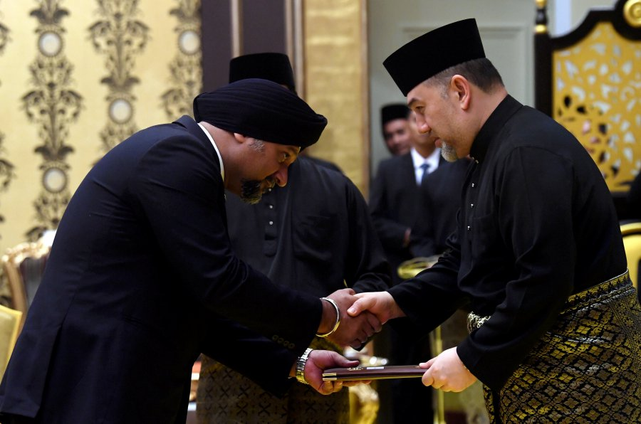 Yang di-Pertuan Agong Sultan Muhammad V presents the instrument of appointment to Communications and Multimedia Minister Gobind Singh Deo during the swearing in ceremony at Istana Negara. Bernama pic.