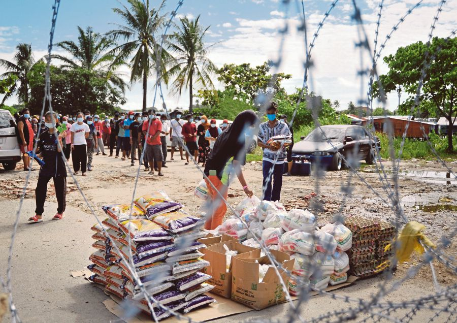 Food baskets being distributed to people in   Saguking Laut and Sebor Baru,  Labuan, yesterday. -BERNAMA pic