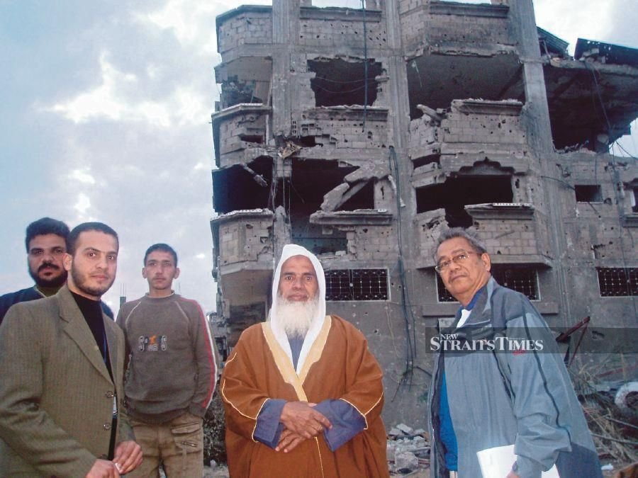 The writer in Gaza 15 years ago. The robed Palestinian is the owner of the ruined building in the background.