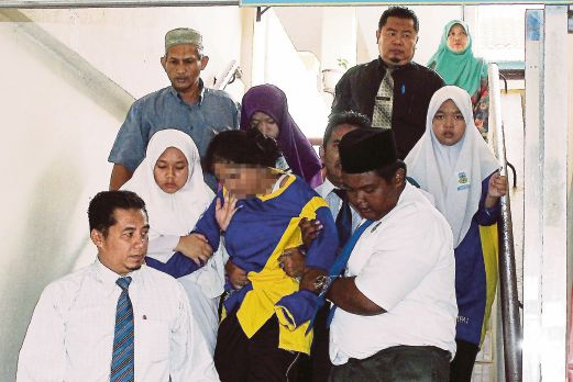 Students and teachers of SMK Pengkalan Chepa 2 in Kota Baru accompanying a student struck by hysteria on Monday.